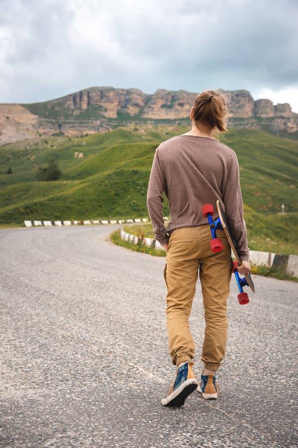 Giovane uomo alla moda dei pantaloni a vita bassa con capelli lunghi ed in occhiali da sole che cammina con un longboard in sue m immagini stock libere da diritti