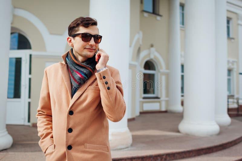 giovane uomo alla moda facendo uso dello smartphone in città Tipo bello che indossa i vestiti e gli accessori classici Modo della immagine stock