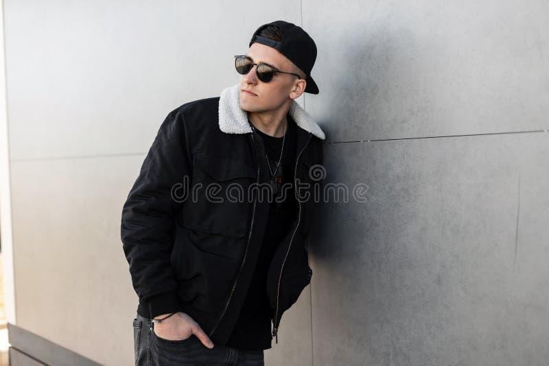Giovane uomo alla moda moderno dei pantaloni a vita bassa in un rivestimento nero alla moda in un cappuccio alla moda in occhiali fotografia stock libera da diritti