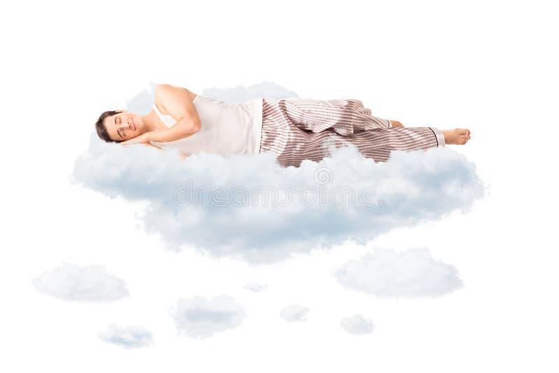 Giovane uomo allegro che dorme su una nuvola fotografia stock