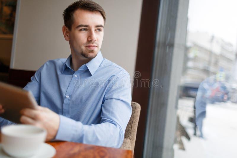 Giovane uomo ambizioso che guarda meditatamente dalla finestra del caffè immagine stock