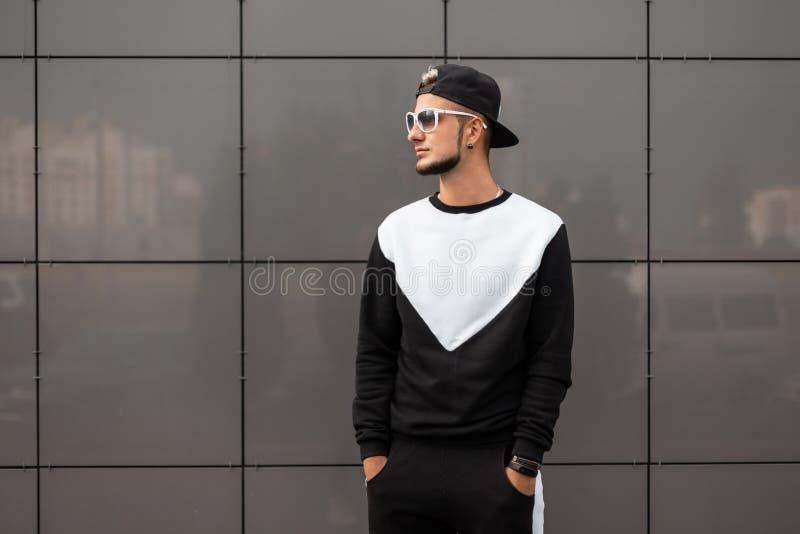 Giovane uomo americano dei pantaloni a vita bassa in berretto nero alla moda in occhiali da sole d'avanguardia nel supporto alla  fotografia stock