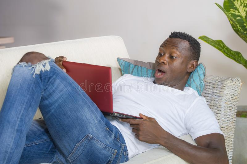 Giovane uomo americano emozionante e sorpreso del giovane africano nero nella rete di espressione del fronte di scossa e di incre fotografie stock libere da diritti
