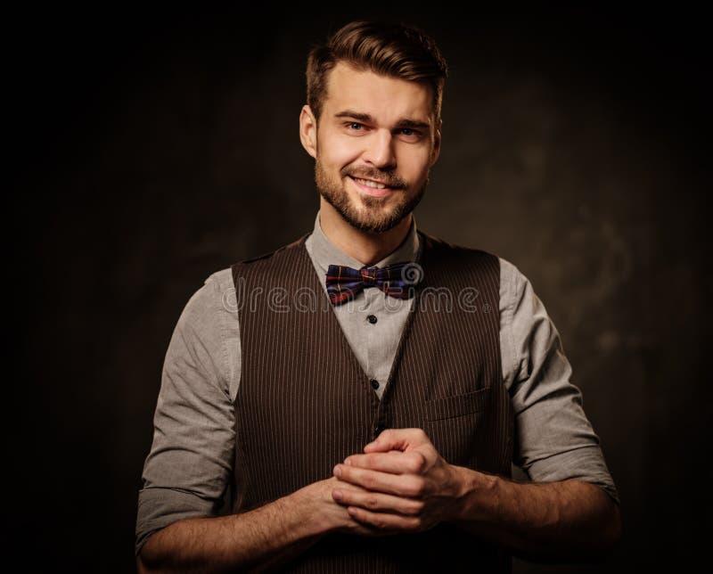 Giovane uomo antiquato bello con la barba che posa sul fondo scuro fotografie stock