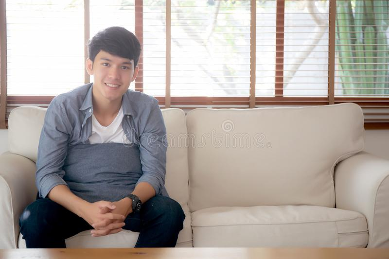 Giovane uomo asiatico bello del ritratto che fa un sonnellino per rilassarsi con accogliente sul sofà a casa, riposo maschio dell fotografia stock