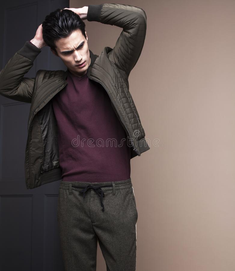 Giovane uomo asiatico bello reale fresco in cappotto su fondo nero p fotografia stock