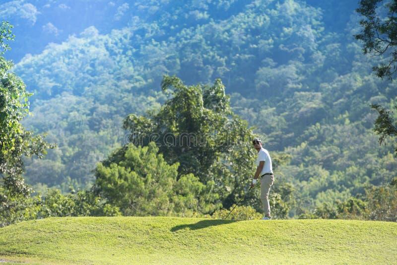 Giovane uomo asiatico che gioca golf su un bello campo da golf naturale immagine stock