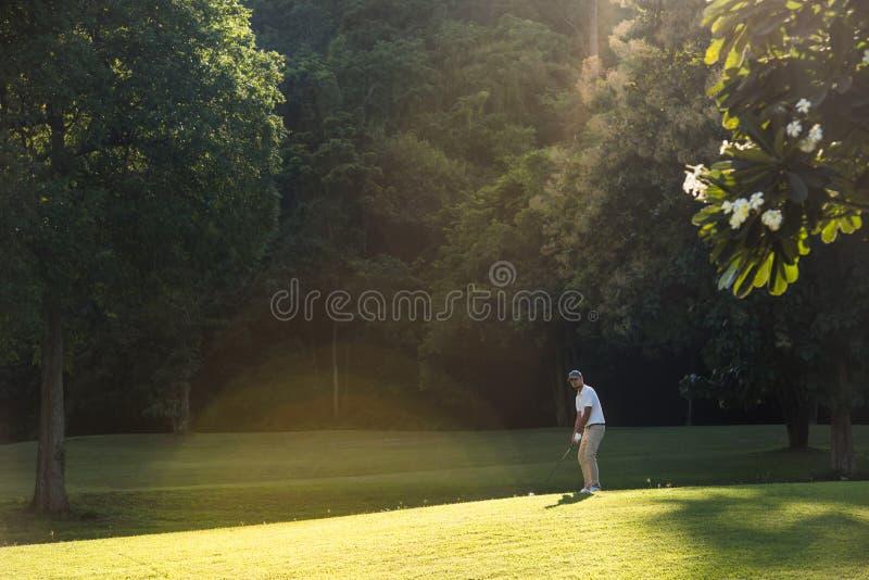 Giovane uomo asiatico che gioca golf su un bello campo da golf naturale immagini stock libere da diritti