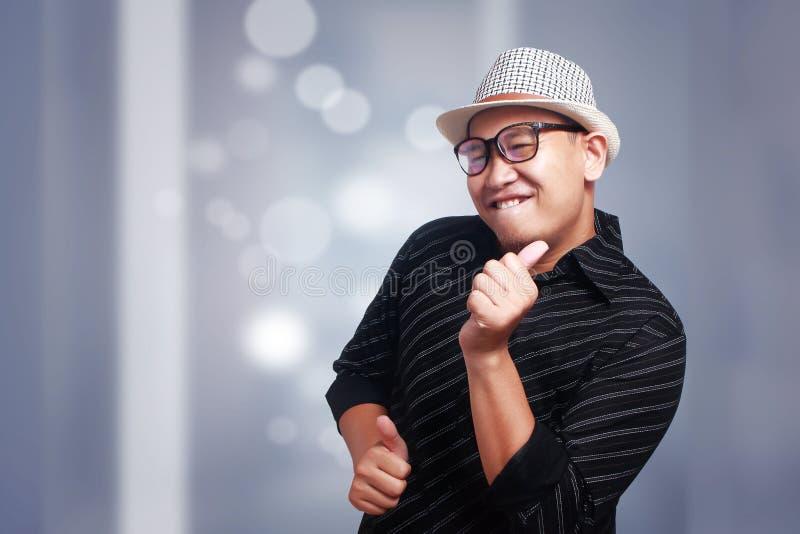 Giovane uomo asiatico che indossa Havana Hat Smiling Dancing immagine stock libera da diritti