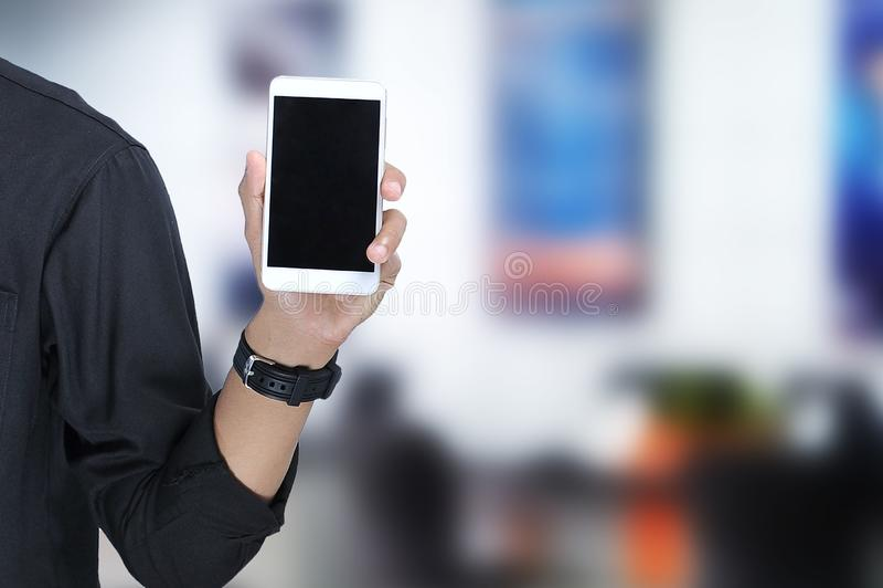 Giovane uomo asiatico che mostra lo schermo in bianco dello smartphone fotografia stock libera da diritti