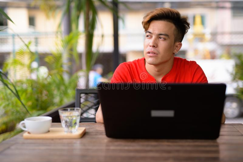 Giovane uomo asiatico che pensa mentre facendo uso del computer portatile alla caffetteria all'aperto immagine stock libera da diritti