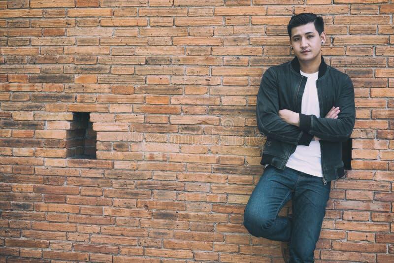 giovane uomo asiatico che porta rivestimento nero e le blue jeans che stanno aga fotografia stock libera da diritti
