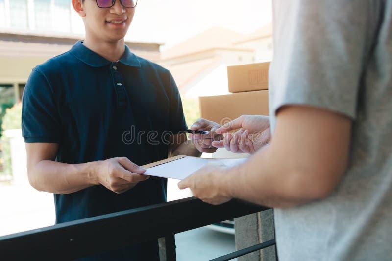Giovane uomo asiatico che sorride mentre consegnando una scatola di cartone al documento della tenuta della donna alla firma di f immagine stock libera da diritti