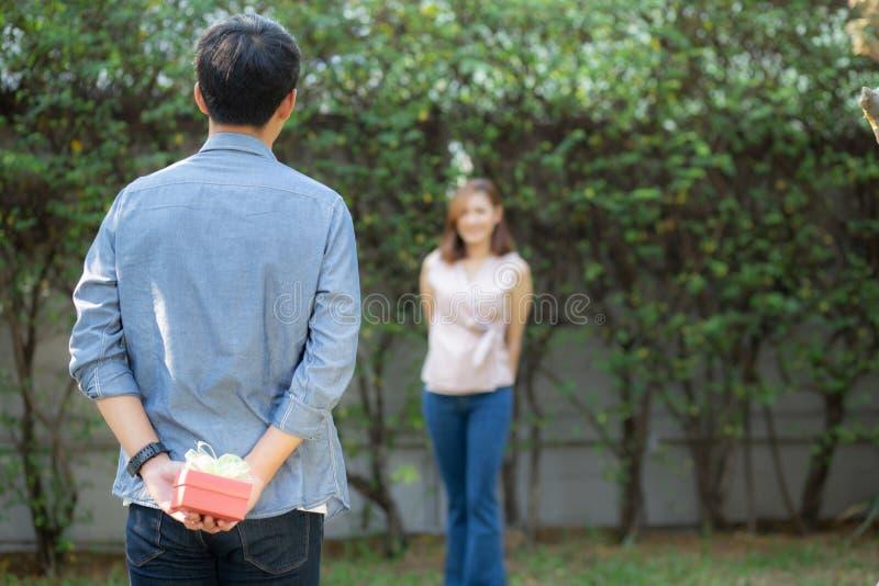 Giovane uomo asiatico che tiene dietro l'amica posteriore di sorpresa del contenitore di regalo eccitata nel giardino con felice, fotografia stock libera da diritti