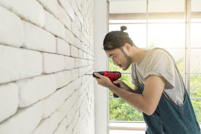 Giovane uomo asiatico che utilizza trapano elettrico sul muro di mattoni bianco nella stanza fotografia stock libera da diritti