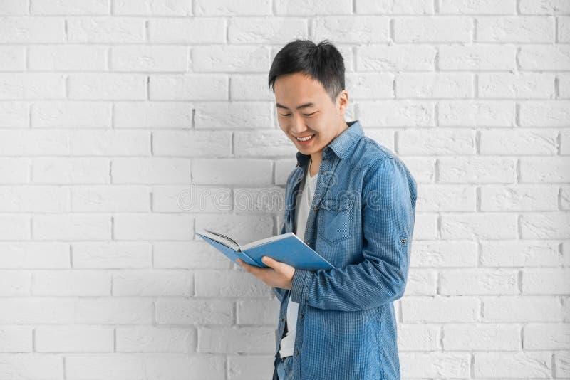 Giovane uomo asiatico con il muro di mattoni diritto del libro fotografie stock