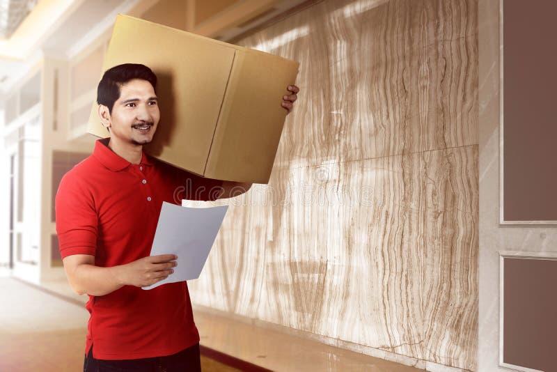 Giovane uomo asiatico del corriere con la scatola che cerca il destinatario del pacchetto fotografia stock
