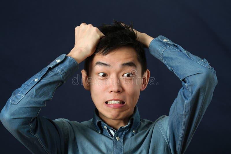Giovane uomo asiatico deludente che fa fronte fotografie stock libere da diritti