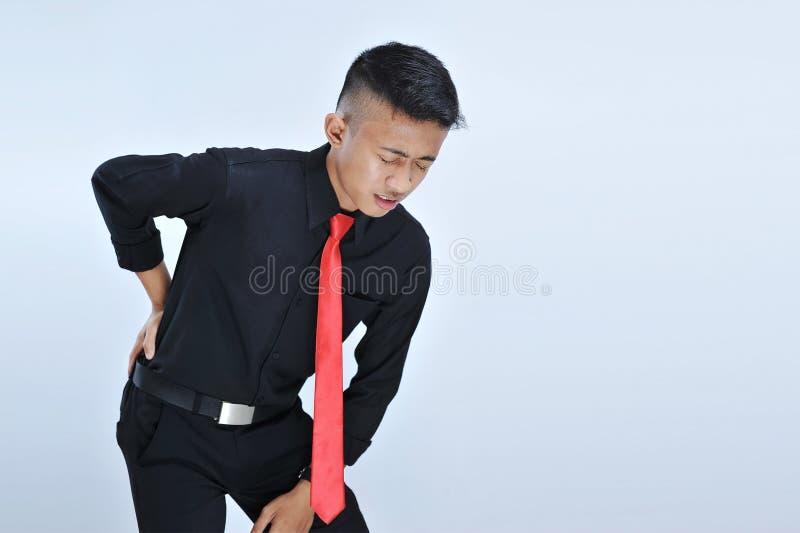 Giovane uomo asiatico di affari che ha dolore alla schiena fotografie stock libere da diritti