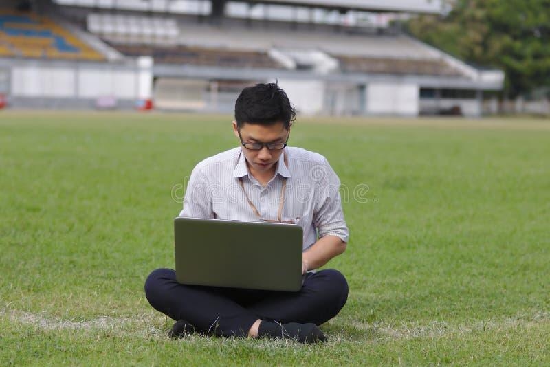 Giovane uomo asiatico rilassato di affari che lavora con il computer portatile su erba verde immagini stock