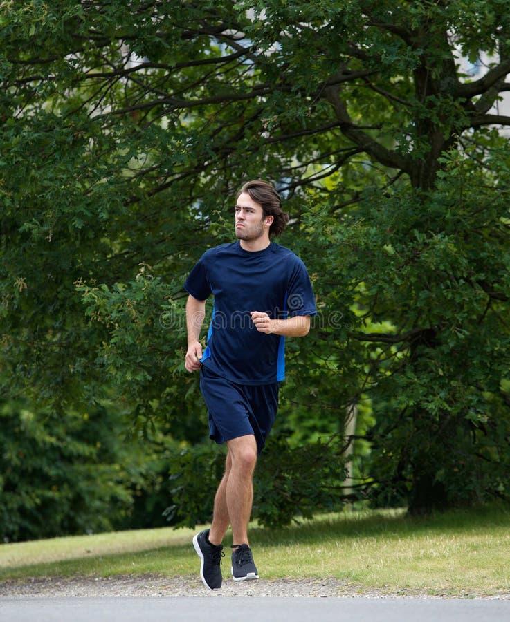 Giovane uomo atletico che corre all'aperto fotografie stock libere da diritti