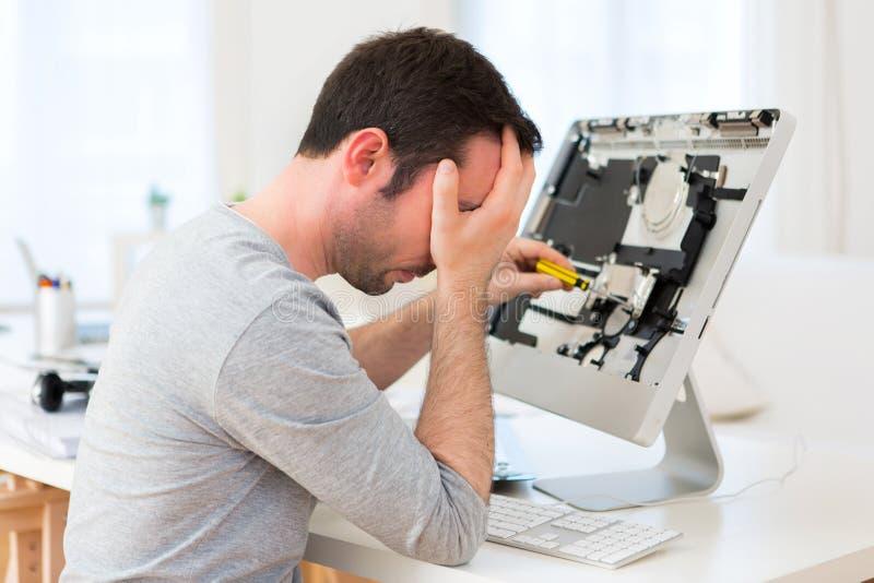 Giovane uomo attraente che prova a riparare computer fotografia stock