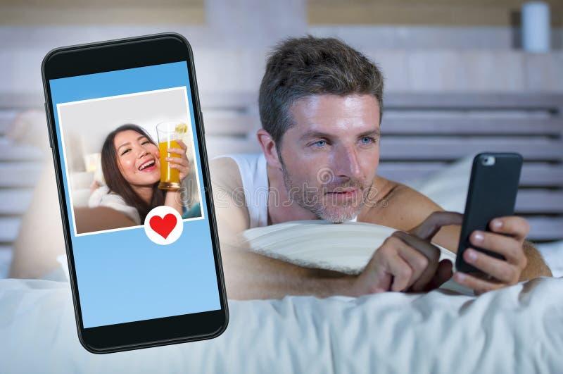 Giovane uomo attraente che si trova a letto sulla linea che cerca il sesso o sull'amore che scopre che un bello profilo della rag fotografia stock