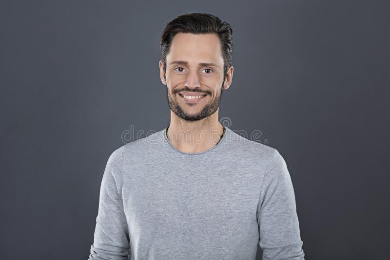 Giovane uomo attraente con sorridere grigio della maglietta felice davanti ad un fondo grigio immagine stock