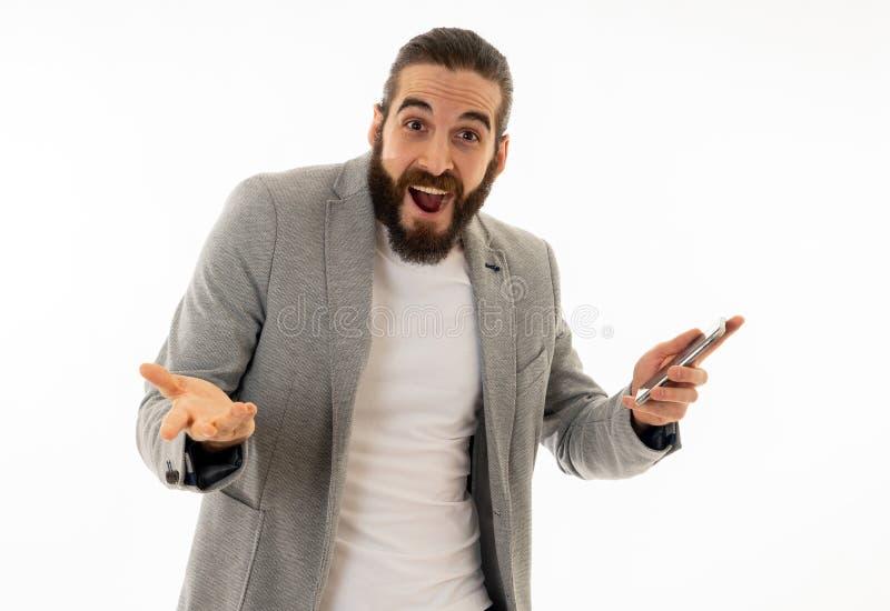 Giovane uomo attraente dei pantaloni a vita bassa che esamina perdita colpita e sorpresa dello Smart Phone mobile dei simili immagini stock libere da diritti