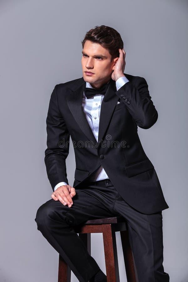 Giovane uomo attraente di affari che ripara i suoi capelli fotografie stock