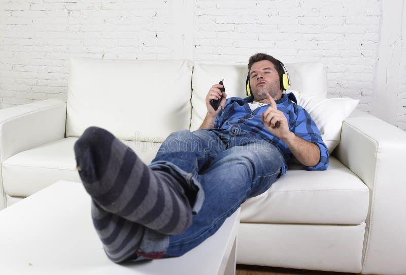 Giovane uomo attraente divertendosi da solo menzogne sullo strato che ascolta la musica con il telefono cellulare e le cuffie fotografia stock libera da diritti