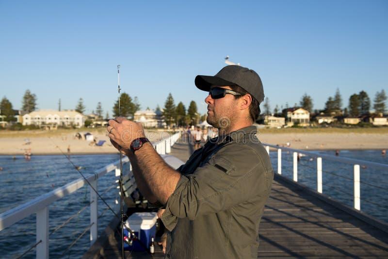 Giovane uomo attraente e felice nella pesca del cappello e della camicia al bacino del mare della spiaggia facendo uso della stra immagini stock libere da diritti