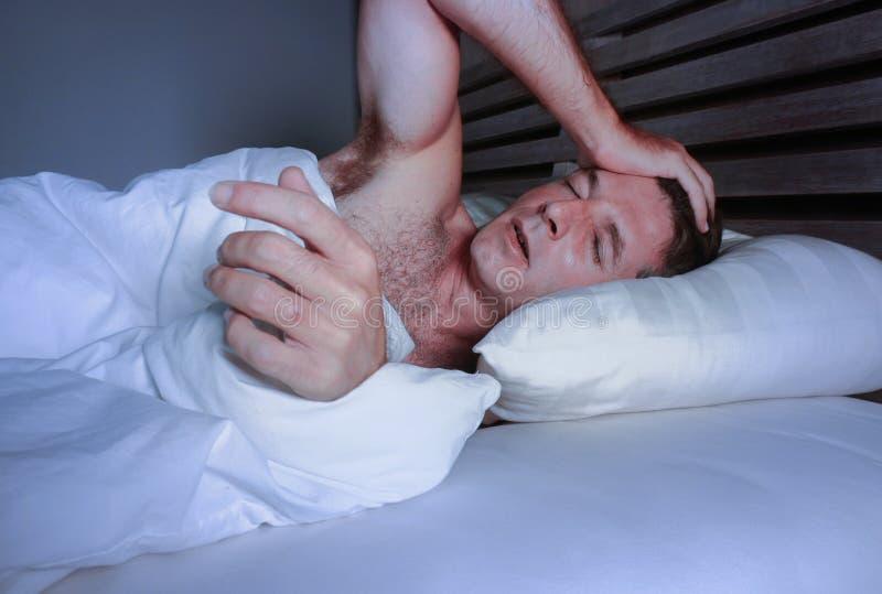 Giovane uomo attraente preoccupato agitato sveglio alla notte che si trova sul letto insonne con l'ampio diso di sofferenza apert immagine stock libera da diritti
