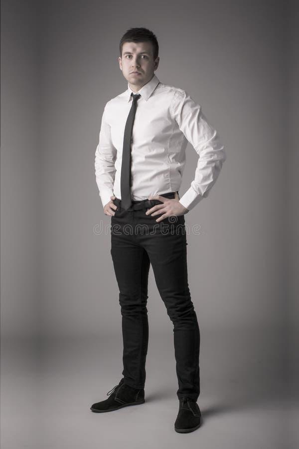 Giovane uomo azzimato di affari con le mani sulle anche immagini stock