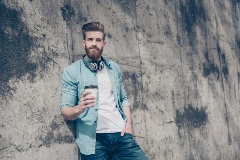 Giovane uomo barbuto alla moda felice in camicia dei jeans con i heanphones o fotografia stock libera da diritti