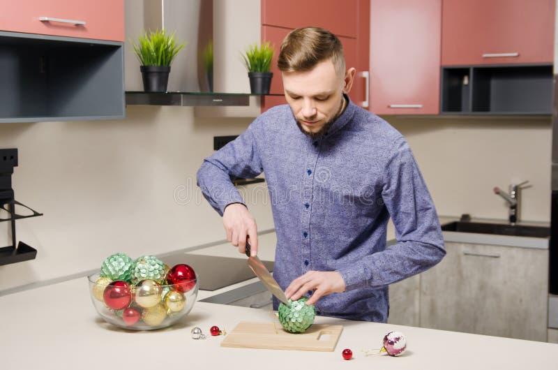 Giovane uomo barbuto attraente che cucina la cena del nuovo anno festivo L'uomo prepara l'insalata delle palle decorate di Natale fotografie stock