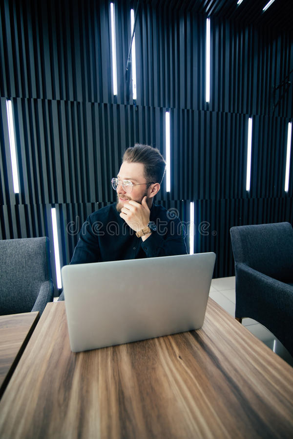 Giovane uomo barbuto attraente in vestito che distoglie lo sguardo mentre sedendosi alla scrivania con il computer portatile ed a fotografia stock