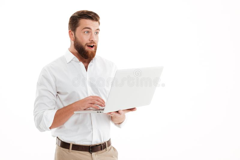 Giovane uomo barbuto bello che per mezzo del computer portatile fotografia stock libera da diritti