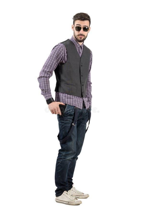 Giovane uomo barbuto che mette il suo telefono cellulare in sua tasca fotografia stock