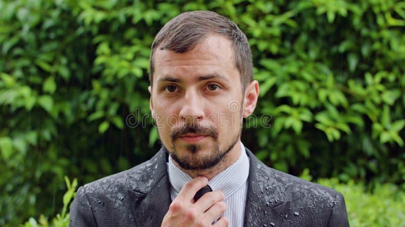 Giovane uomo barbuto che sta nella pioggia immagine stock libera da diritti