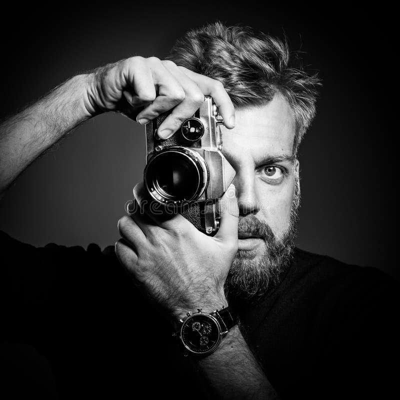 Giovane uomo barbuto che tiene retro macchina fotografica immagine stock libera da diritti