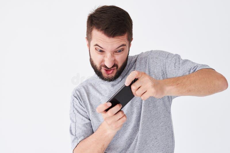 Giovane uomo barbuto emozionale che gioca sullo smatphone fotografia stock libera da diritti