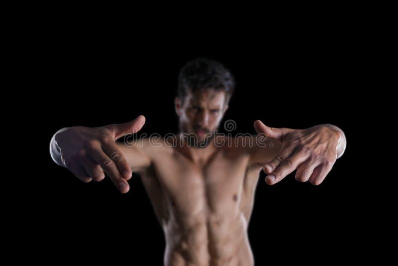 Giovane uomo barbuto sexy che posa fingendo fucilazione con il dito Gu fotografia stock libera da diritti