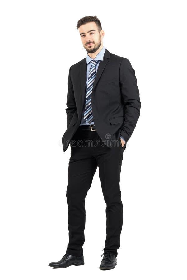 Giovane uomo barbuto sicuro di affari in vestito che esamina macchina fotografica fotografia stock