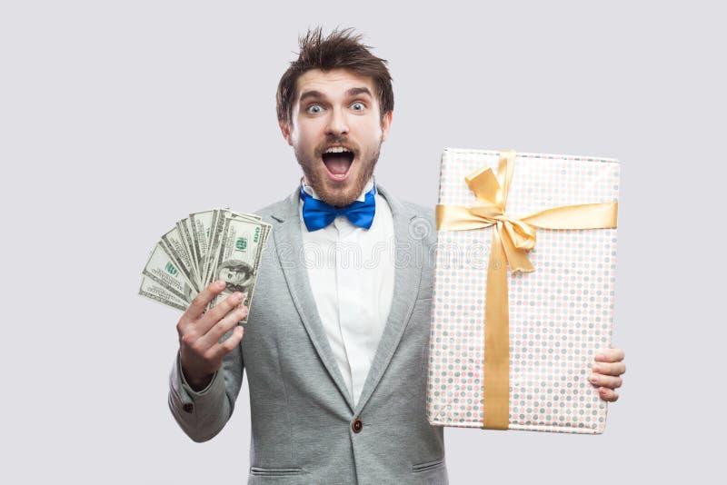 Giovane uomo barbuto sorpreso bello in vestito grigio e nella condizione blu della cravatta a farfalla e nella tenuta del conteni immagini stock