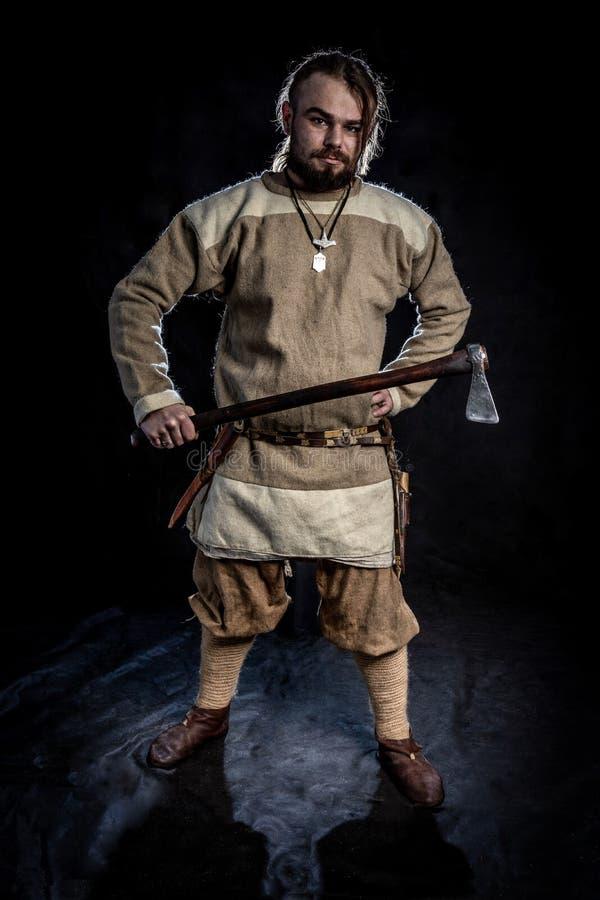 Giovane uomo barbuto in un abbigliamento di età di vichingo che tiene un'azza immagine stock libera da diritti