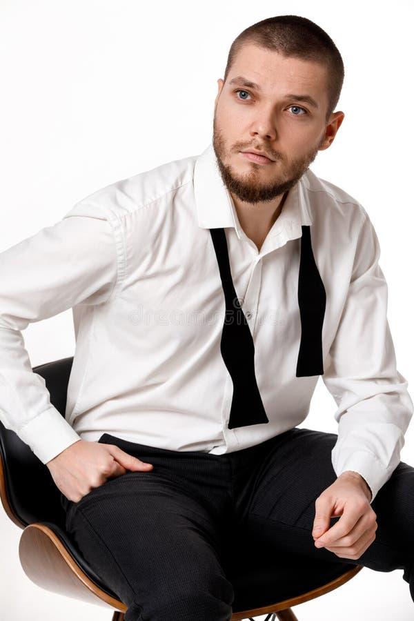 Giovane uomo barbuto in una camicia ed in una cravatta a farfalla bianche immagini stock libere da diritti