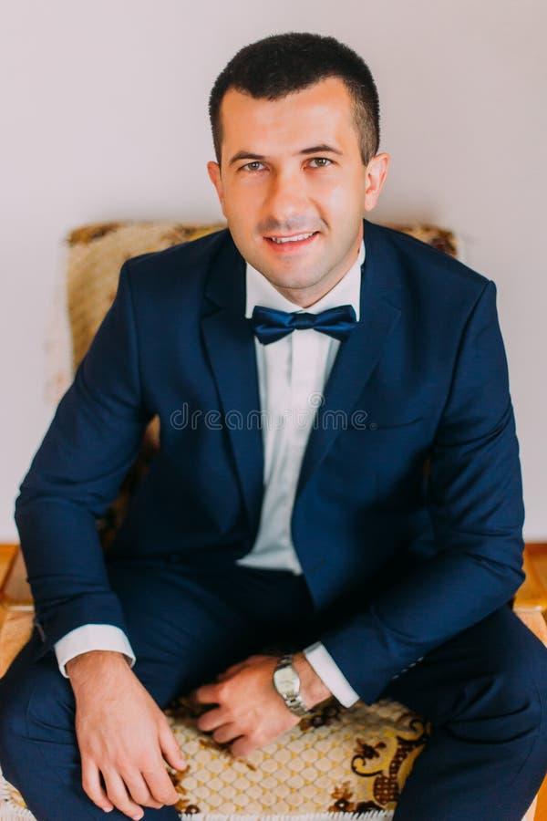 Giovane uomo bello alla moda e sicuro in vestito blu scuro con il farfallino che si siede nella sedia d'annata contro il fondo gr fotografia stock libera da diritti