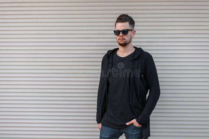 Giovane uomo bello brutale dei pantaloni a vita bassa con una barba in una maglietta alla moda in una maglia con cappuccio nera a fotografia stock