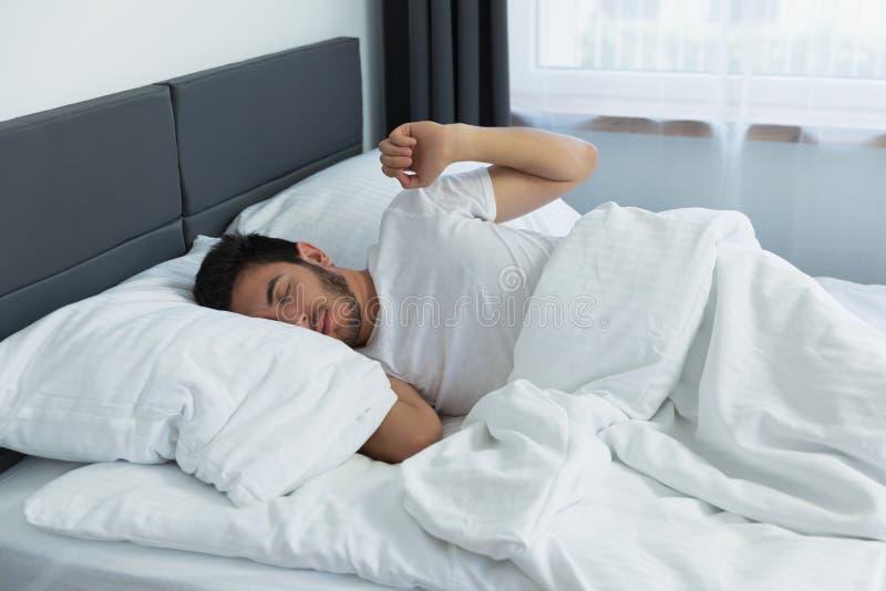 Giovane uomo bello che dorme nel suo letto immagini stock